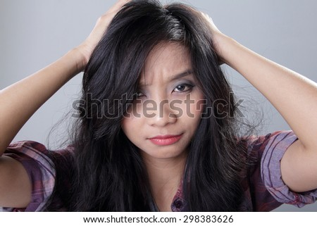 Face of frustrated woman pulling her hair with both hands while looking at camera, on grey background - stock photo