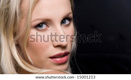 Face of glamorous young woman looking at camera on black background - stock photo