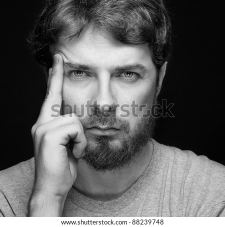 Face of handsome bearded confident young guy over black - stock photo