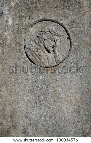 Face of Jesus Christ on cement tomb stone with copy space - stock photo