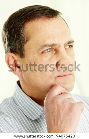 Face of mature man touching his chin and looking forward - stock photo