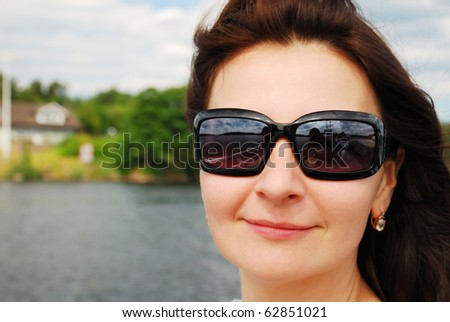 Face of pleased woman is photographed in rural areas. There are river and riverside with house in the background. Focus is on the person.