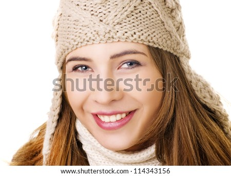 Face of pretty woman in knitted winter cap and scarf