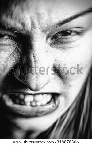 Face of stressed angry woman with scary expression - stock photo