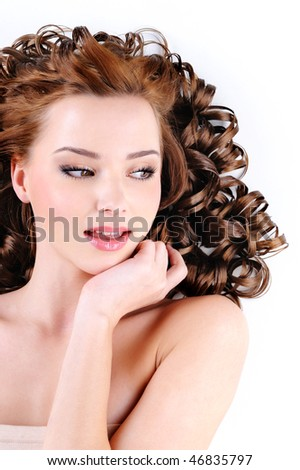 Face of the attractive young woman with  long ringlets hairs - stock photo