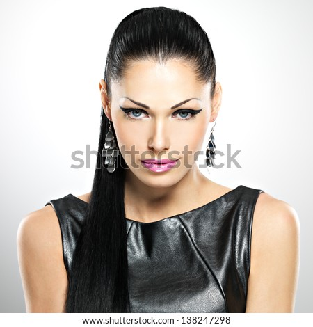 Face of the  beautiful sexy  woman with glamour fashion makeup of eyes and gloss hairstyle. Portrait of the caucasian adult girl at studio