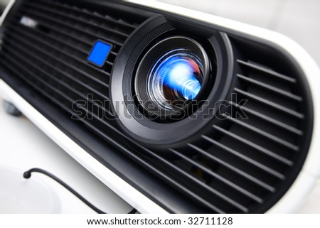 Face of white multimedia projector. Close-up lens. Nobody. Tilt view with shallow DOF. - stock photo