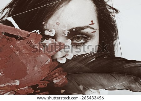 Face of young beautiful woman with a feather behind grid and glass - stock photo