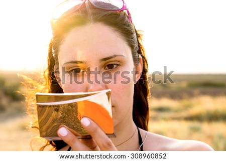 Face of young brunette girl with cosmetic mirror in bright sun rays warm filtered