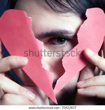 Face of young handsome man with broken paper heart closeup - stock photo