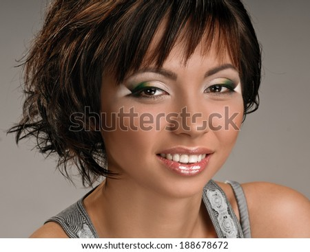 face of young woman with makeup and short hair on grey background - stock photo