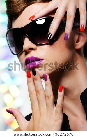 Face of young woman with multicolored manicure and fashion stylish sunglasses - colored background