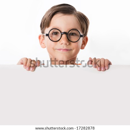 Face of youthful boy in glasses looking from behind white partition - stock photo