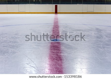 Face off blue spot with red line on hockey rink - stock photo