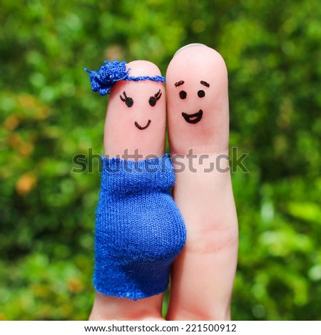 Face painted on fingers. Happy couple, the woman is pregnant.  - stock photo