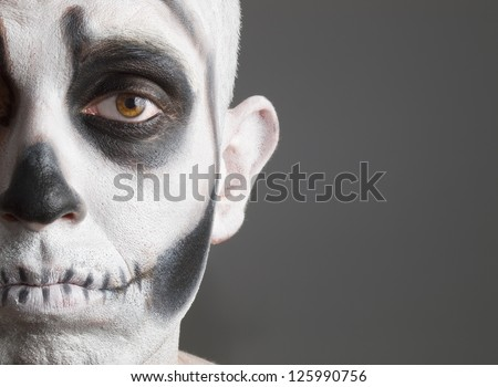 face painted with a skull. The photo shows a young man with painted face face painted with a skull. - stock photo