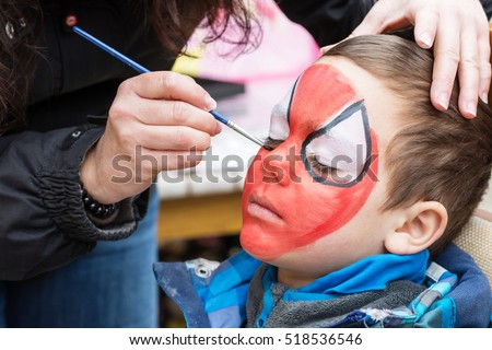 Face painting artist painting a child as spider man.