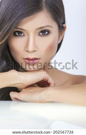 Face portrait of a beautiful nude sexy young Chinese Asian woman or girl resting on her hands - stock photo