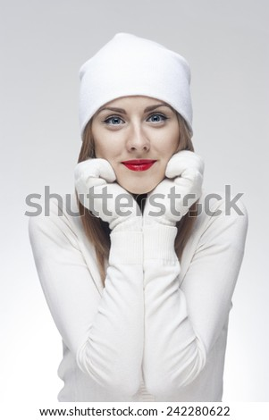 Face portrait of a young beautiful woman in white knit wool hat and mittens isolated on a light background. - stock photo