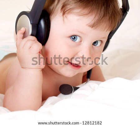 face portrait of beautiful baby with headset - stock photo