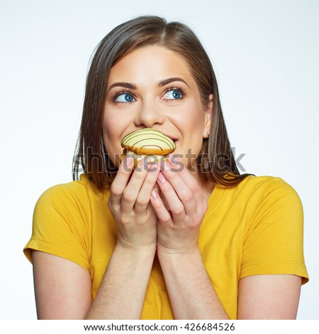 Face portrait of smiling woman biting cake. Happy model close up isolated portrait. - stock photo