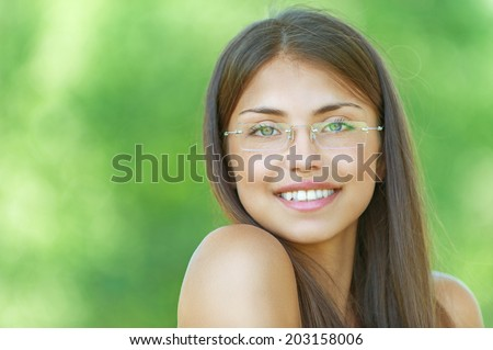 Face young beautiful girl dark closeups short hair glasses summer park smiling - stock photo
