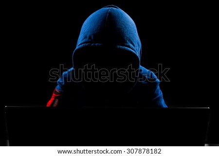 Faceless hacker with laptop in black isolated background. - stock photo