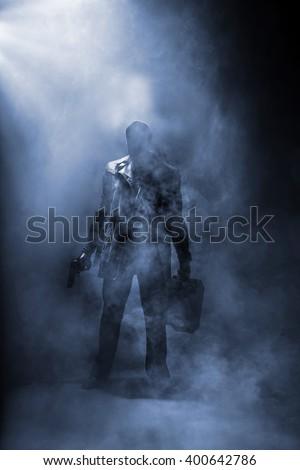 Faceless man holding a gun and a briefcase standing in haze. - stock photo