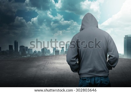 Faceless man in hood on the rooftop with city background - stock photo