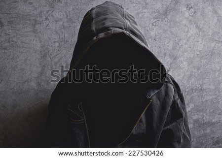 Faceless unknown and unrecognizable man without identity wearing hood in dark room, spooky criminal person. - stock photo