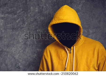 Faceless unknown and unrecognizable person without identity wearing yellow hooded jacket. - stock photo