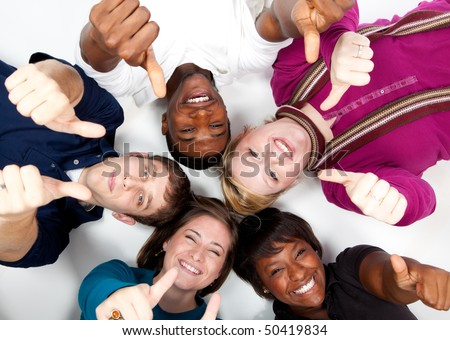 faces of smiling multi-racial college students/friends with their thumbs up - stock photo