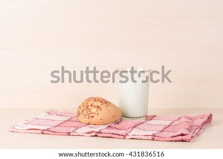 Faceted glass of fresh milk and a bun on a red squared kitchen towel on light wooden textured background. - stock photo