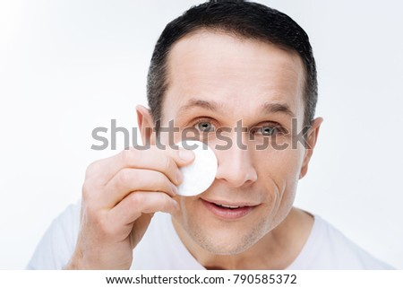 Facial care. Portrait of a nice handsome positive man holding a cotton pad and smiling while cleaning his face with a cotton pad