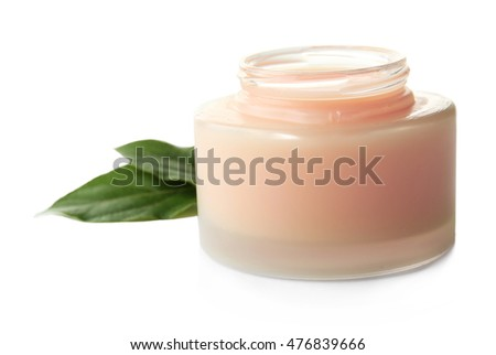 Facial cream and green leaves on white background