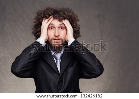 facial expression of a young businessman who has troubles on grunge background - stock photo