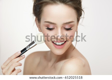 Facial Makeup. Closeup Of Beautiful Young Female Model Putting Blush With Cosmetic Brush. Portrait Of Attractive Healthy Girl With Pure Clean Skin And Natural Make-Up. Beauty Concept. High Resolution