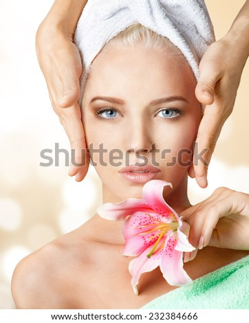 Facial massage of beautiful young woman in spa.  - stock photo