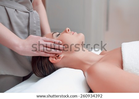 Facial massage. Top view of attractive young woman lying on back and keeping her eyes closed while massage therapist massaging her face - stock photo