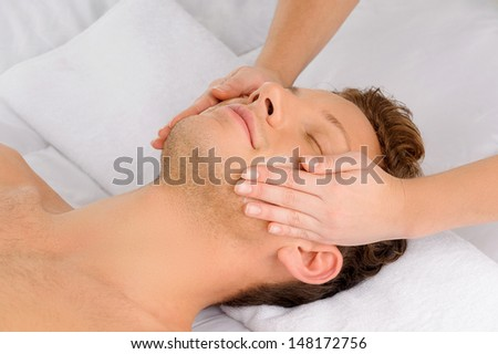 Facial massage. Top view of relaxed young men lying on the massage table while massage therapist massaging his face - stock photo