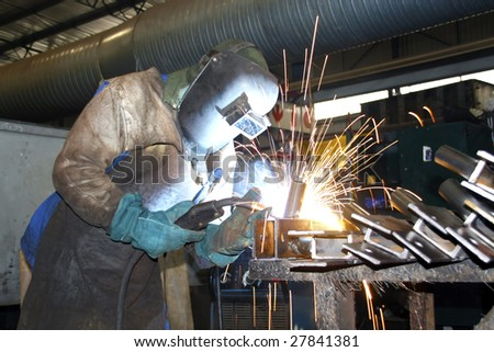 Factory Artisan wearing protective gear while arc welding metal