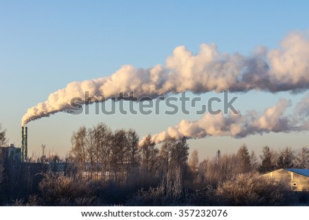 factory chimneys and coming out white smokes in the blue sky background - stock photo