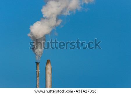 factory chimneys with smoke against blue sky - stock photo