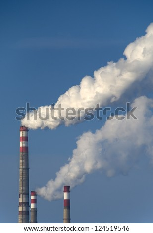 factory chimneys with white smoke against a blue sky