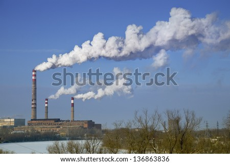 factory chimneys with white smoke against a blue sky - stock photo