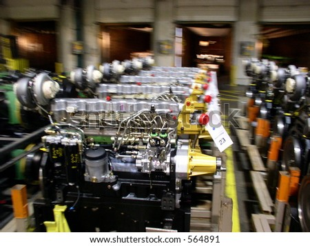 Factory floor in automotive plant has row after row of new engines waiting to be installed - stock photo