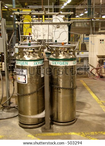 Factory floor oxygen cylinders used in industrial processes.