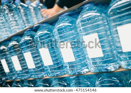 Factory for purification and bottling of drinking water into bottles and canisters. Full water canisters ready for shipment. Place for text.