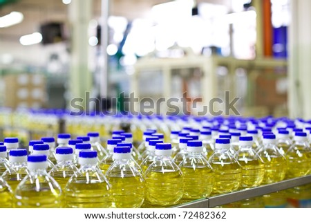 Factory for the production of edible oils. Shallow DOFF. Selective focus. The focus is on the bottle in the center down. - stock photo