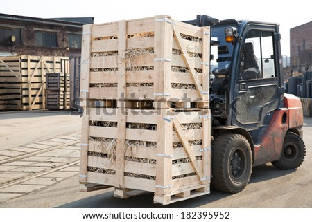 Factory Forklift Truck Stacker Transporting Wood Cargo Boxes with Products to Plant Warehouse - stock photo